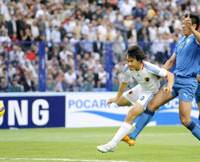 Man of the hour: Japan forward Shinji Okazaki (9), seen taking a first-half shot against Uzbekistan, notched the match-winning goal off the rebound in the ninth minute against the hosts in a World Cup qualifier on Saturday night in Tashkent. Japan defeated Uzbekistan 1-0 and qualified for the World Cup finals for the fourth straight time.   KYODO PHOTOS