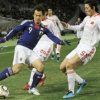 On the run: Japan forward Shinji Okazaki controls the ball as China defender Zhao Peng (right) surveys his next move during the East Asian Football Championship's opening match on Saturday at Ajinomoto Stadium. The match ended in a scoreless draw. | KYODO PHOTO