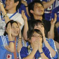 Half a world away: Japan soccer fans watch Saturday's Group E match during a public gathering in Tokyo. | KYODO PHOTO