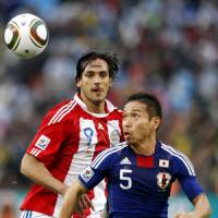 Locking horns: Japan's Yuto Nagatomo eyes the ball while Paraguay's Roque Santa Cruz moves in behind him during their World Cup second-round match in Pretoria on Tuesday.   AP PHOTO