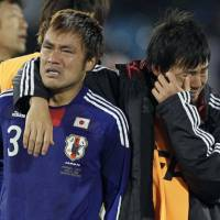 Feeling blue: Yuichi Komano (left) and Daisuke Matsui try to come to terms with Japan's 5-3 penalty shootout loss to Paraguay in Pretoria on Tuesday. The South Americans progressed to the World Cup quarterfinals after Komano missed his spot kick. | AP PHOTO