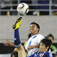 Acrobatic play: Japan midfielder Shinji Kagawa attempts an overhead kick against a Guatemala defender in Tuesday's international friendly match at Nagai Stadium. | KYODO PHOTO
