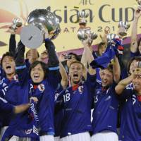 Japan's players celebrate winning the Asian Cup after beating Australia 1-0 in the final in Doha on Saturday. Tadanari Lee's winning goal in extra time gave Japan a record fourth continental title. | KYODO PHOTO