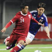 Foot clash: Peru midfielder Christian Cueva (left) and Japan midfielder Daigo Nishi vie for the ball during Wednesday's international friendly in Niigata. The match ended 0-0. | KYODO