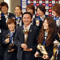 Triumphant return: Japanese women's soccer coach Norio Sasaki (center) holds the Women's World Cup trophy as he poses for a photograph with the team during a news conference in Tokyo on Tuesday. | AP