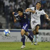 Honors even: Japan's Atsuto Uchida tries to break clear of Uzbekistan's Odil Akhmedov in Tashkent on Tuesday. | AP