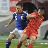 Competitive fire: Japan's Yuto Nagatomo (left) and a Vietnam player vie for the ball in first-half action on Friday in Kobe. Japan beat Vietnam 1-0. | KYODO