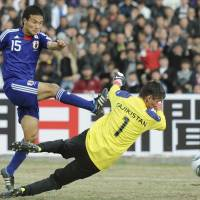 Successful start: Japan's Yasuyuki Konno scores a 36th-minute goal past Tajikistan goalkeeper in Friday's 2014 World Cup qualifier in Dushanbe. Japan beat the hosts 4-0.   KYODO