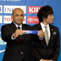 Lucky dip: Former national team defender Tsuneyasu Miyamoto looks on as AFC executive director Windsor John pulls out the name of one of Japan's World Cup opponents on Friday. | AP