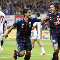 First strike: Yasuhito Endo celebrates his goal with teammate Shinji Okazaki during Japan's 1-1 draw against Venezuela. | KYODO