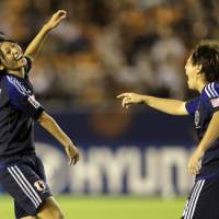 Moving on: Japan's Yoko Tanaka (left) celebrates with teammate Kumi Yokoyama after scoring against Switzerland on Sunday. Japan won 4-0 to advance to the quarterfinals of the Women's Under-20 World Cup. | AP