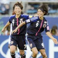 Feeling great: Yoko Tanaka (above right) celebrates her 24th-minute goal with teammate Nozomi Fujita during Saturday's Under-20 Women's World Cup third-place match against Nigeria at National Stadium. Young Nadeshiko defeated Nigeria 2-1.  (Below): Japan's Kumi Yokoyama (10) competes with Nigeria's Blessing Edoho for the ball in Saturday's match. | KYODO