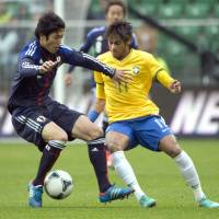 On another level: Atsuto Uchida (left) competes for the ball with Neymar during Brazil's 4-0 victory over Japan on Tuesday in Wroclaw, Poland. | AFP-JIJI