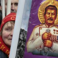 Hero of the hardliners: A woman holds a portrait of Soviet dictator Josef Stalin during a rally in Moscow in February. | AP