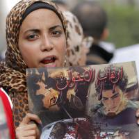 Fighting in the streets: An Egyptian woman participating in a protest rally against the ruling Muslim Brotherhood in Cairo on Saturday holds up a poster showing what she said are victims of Friday night's clashes in the Nile delta city of Mansoura. | AP