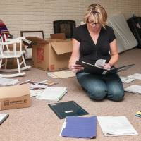 Karen Busser reviews documents related to her husband Paul's work at Byron. | ANDREW BOROWIEC
