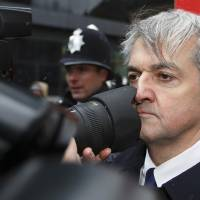 Bumpy road: Former British energy minister Chris Huhne (right) bumps into a photographers' lens as he arrives at Southwark Crown Court in London on Monday. | AFP-JIJI