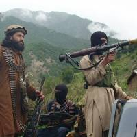 No place like home: Taliban militants patrol their stronghold of Shawal, in Pakistan's South Waziristan tribal region, last August.   AP