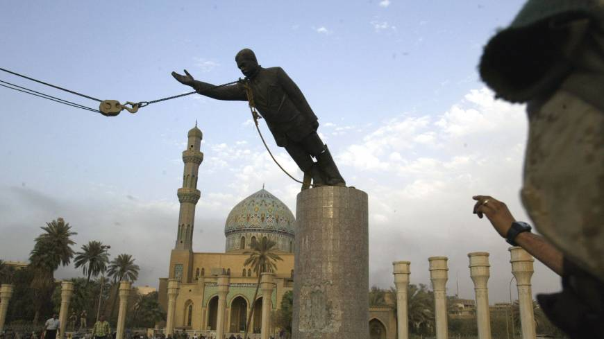 A U.S. Marine watches a statue of Saddam Hussein being toppled in Baghdad's Firdaus Square on April 9, 2003.
