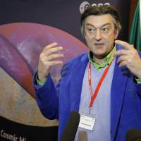 Space quest: French astrophysicist Francois Bouchet speaks to the media at the European Space Agency's headquarters in Paris on Thursday, in front of the most detailed map ever created of the cosmic microwave background.  | AP