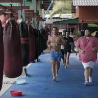 Eye of the tiger: Students work out at the  Tiger muay  Thai & MMA training camp in Phuket,  Thailand. Foreigners are flocking to Thailand to spend the holidays not relaxing, but fighting their way to fitness practicing Muay  Thai and other martial arts. | AFP-JIJI