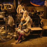 Defining values: A woman waits at a food stall in Delhi. Many Indians say women should not be out at night on their own.