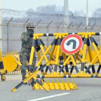 Border battle: A South Korean soldier sets a barricade at a military check point on the road linked to North Korea in Paju, near the Demilitarized Zone on Monday. Pyongyang told Seoul on Wednesday that it was banning access to their Kaesong joint industrial park, but said South Koreans in the complex would be allowed to leave. | AFP-JIJI
