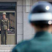 Uneasy peace: Soldiers from North Korea (left) and South Korea stand guard on their respective sides of the border at the truce village of Panmunjom in the demilitarized zone dividing the two countries on Thursday. | AFP-JIJI
