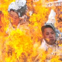 Unliked neighbors: South Korean activists burn effigies of Kim Il Sung (left), North Korea's late founder, and Kim Jong Un, his grandson and current leader, during a rally in Seoul on Monday. | AFP-JIJI