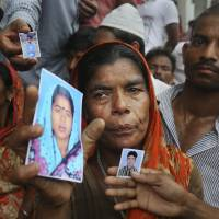 Still hoping: A Bangladeshi weeps as she holds a picture of a missing relative at the ruins of a building that collapsed Wednesday in Savar, on the outskirts of Dhaka. | AP