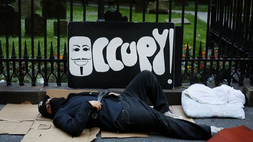 Put to bed: An Occupy Wall Street protester sleeps on the ground before a demonstration in New York on Sept. 17, 2012. | BLOOMBERG