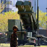 Covering all bases: A soldier of Japan's Ground Self-Defence Force patrols near a Patriot Advanced Capability-3 (PAC-3) missile launcher deployed at the Defence Ministry in Tokyo on April 11, in anticipation of an expected mid-range missile launch by North Korea.   AFP-JIJI