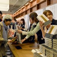 Hot off the press: Fans of Haruki Murakami buy his newly published book, 'Colorless Tsukuru Tazaki and the Year of his Pilgrimage,' at a bookstore in Tokyo on April 12. The store started selling the books for Murakami fans at midnight. | AFP-JIJI