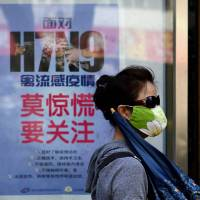 Warning signs: A masked woman in Beijing walks past a poster showing how to avoid the H7N9 avian influenza virus. International experts have said that H7N9 is 'one of the most lethal' strains of avian flu they have seen so far. | AFP-JIJI