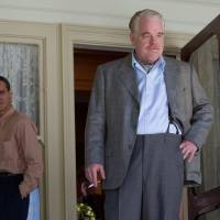 Man in back: Joaquin Phoenix (left) plays Freddie Quell, a former naval officer who is charmed by cult leader Lancaster Dodd, played by Philip Seymour Hoffman (right). | © MMXII BY WESTERN FILM COMPANY LLC ALL RIGHTS RESERVED.