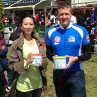 Riding to the rescue: Robert Williams of the Tokyo Brits expat group gathers donations with a volunteer of the Save Minamisoma Project during a sporting event at the Yokohama Country and Athletic Club on Sunday. This was part of fundraising for an upcoming charity cycle ride from Tokyo to Fukushima Prefecture to assist the disaster-hit coastal city. | KYODO