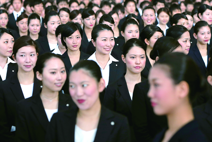 Japan Airlines Co. (JAL) group companies' new employees attend a welcoming ceremony at the company's hangar near Haneda Airport in Tokyo on April 1. | BLOOMBERG