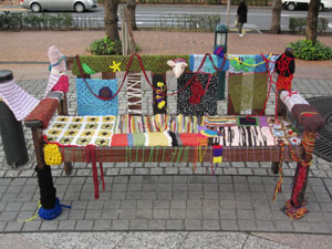 A bench in Ebisu's Yebisu Garden Place, decorated by the Surprise Attack Knitting Group. | © HANAKOMET