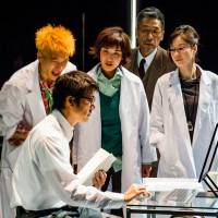 Mr. Efficiency: Ken (Kosuke Toyohara, front) explains the logic of business operation efficiency to two young scientists, chief officer Grant (Suu Nakajima, at rear) and senior scientist Iffy (Yuko Miyamoto, right) in 'The Opportunity of Efficiency.'     © MASAHIKO YAKOU. COURTESY OF NEW NATIONAL THEATRE TOKYO