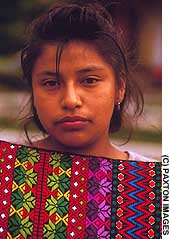 An Antigua local shows off Guatemala's woven crafts.