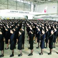 HAPPY LANDINGSNew recruits attend a welcome ceremony Monday in a Japan Airlines Co. hangar at Tokyo's Haneda airport, marking the first new hires at JAL since 2010. | KYODO