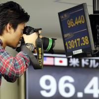 Freeze frame: A photographer takes a picture of the monitors at a foreign exchange company in Tokyo on Friday. | AP