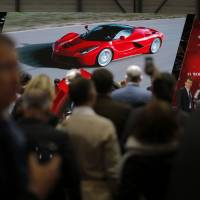 Yen for speed: Visitors watch a video of the new Ferrari La Ferrari (F150) on Ferrari SpA's stand at the 83rd Geneva International Motor Show in Geneva on March 6. | BLOOMBERG