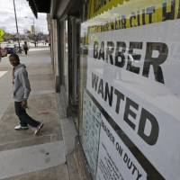 Need a haircut?: A help wanted sign is posted at a barber shop in Richmond, Virginia, on March 29. U.S. employers added just 88,000 jobs in March, the fewest in nine months. Many discouraged Americans are giving up their job hunts for school, retirement or disability. | AP