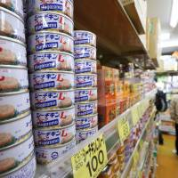 Cans of Hagoromo Foods Corp.'s Sea Chicken tuna product are stacked at a Tokyo supermarket Tuesday. The food maker has said it will raise the price of the long-running popular product by as much as 6 percent in May due to the rising material costs and weakening yen. | BLOOMBERG
