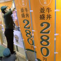 Anti-inflationary: Employees at a Yoshinoya 'gyudon' beef-on-rice bowl outlet near JR Yurakucho Station in central Tokyo put up signs Thursday morning advertising yet another price reduction for a regular serving. | KYODO