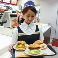 Ready to launch: A McDonald's employee shows off three new products during a press event earlier this month. McDonald's Holdings Co. Japan Ltd. announced Thursday that prices for some items will rise next month. | KYODO