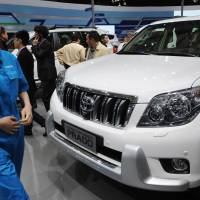Rough ride to recovery: Visitors look at a Toyota Landcruiser Prado SUV on media day at the Shanghai auto show Saturday.   AFP-JIJI
