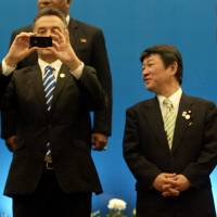 Inside looking out: Australian trade minister Craig Emerson takes a photo with his mobile phone as his Japanese counterpart, Toshimitsu Motegi, looks on during a photo session after the APEC trade ministers' meeting in Surabaya, Indonesia, on Saturday. | AFP-JIJI