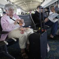 No sweater: A delayed passenger knits to pass the time at  Tampa International Airport on Monday. | AP